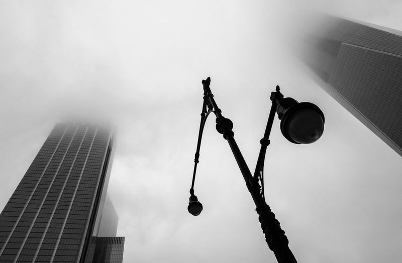 Low angle view of street light and buildings against cloudy sky