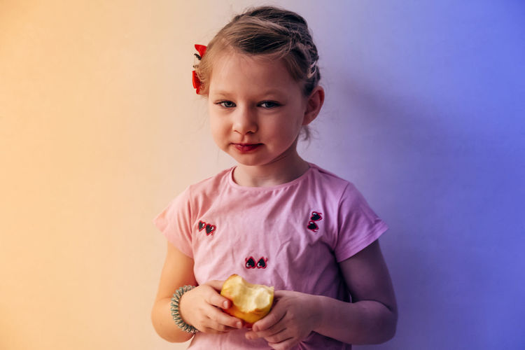 Portrait of a girl holding apple against gray background
