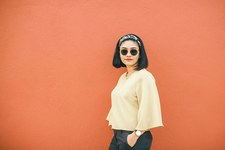 Portrait of young woman in sunglasses standing against wall
