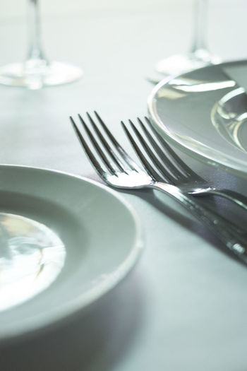 Close-up of forks by plates on table