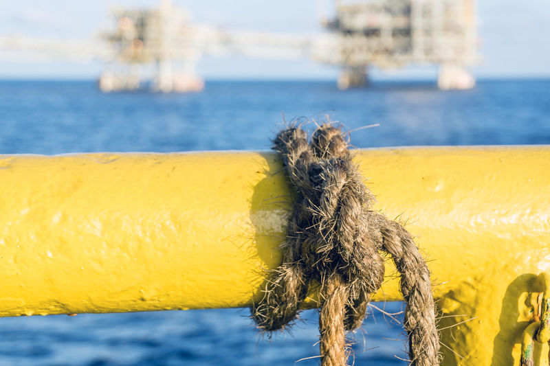 knotted rope on a handrail Upstream Installation Construction Close-up Focus On Foreground Oil And Gas Industry Platform Sea Nautical Maritime Sea Ocean Horizon Barge Vessel Knot Knotted Rope Handrail  Yellow Oil Field