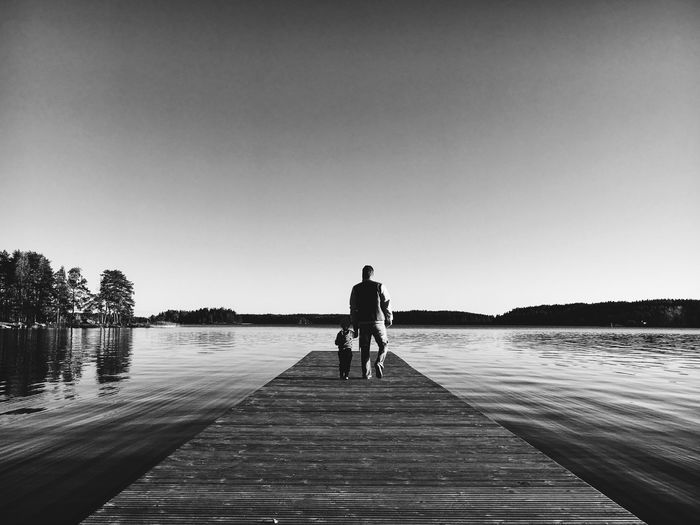 Rear view of man standing on pier over lake against clear sky