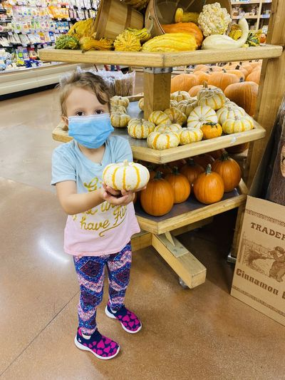 Full length of girl standing by pumpkin at store