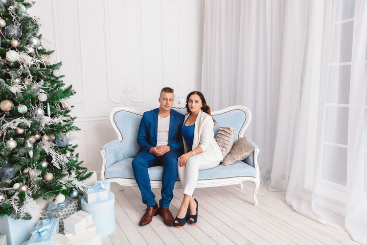 Portrait of couple sitting on sofa by christmas tree at home