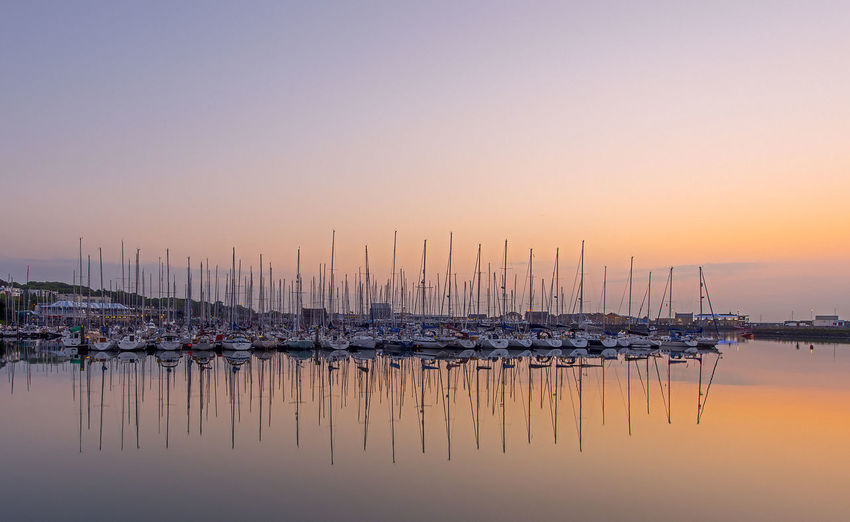 Reflection Of Sailboat Moored In Calm Sea Against Clear Sky During Sunset
