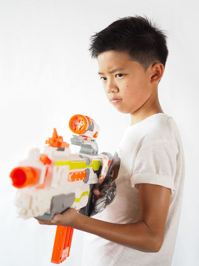 Boys Casual Clothing Childhood Close-up Day Elementary Age Game Holding Home Interior Indoors  Looking At Camera One Person Playing Portrait Real People Standing Studio Shot White Background Asian Boy Toy Guns Toys