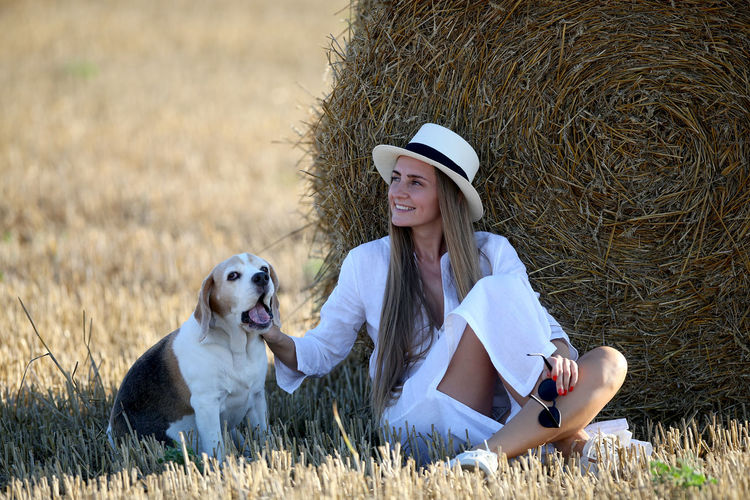 Woman with dog sitting on field