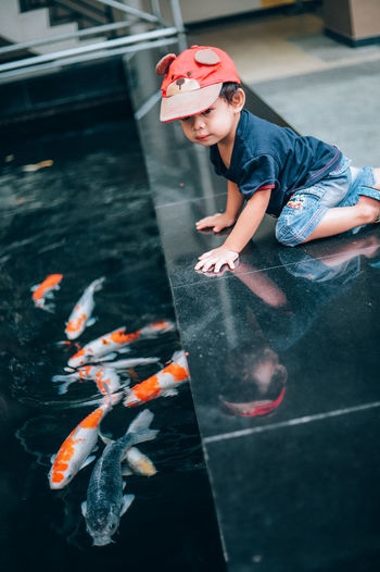 Cute girl looking at fishes in swimming pool