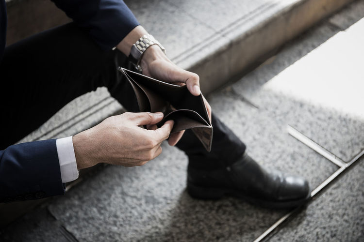 Low section of man holding empty wallet while sitting on floor