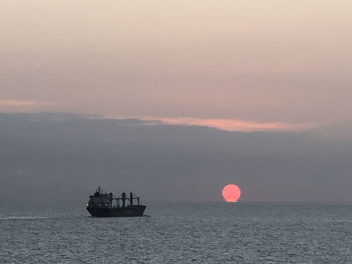 Boat sailing on sea against sky during sunset