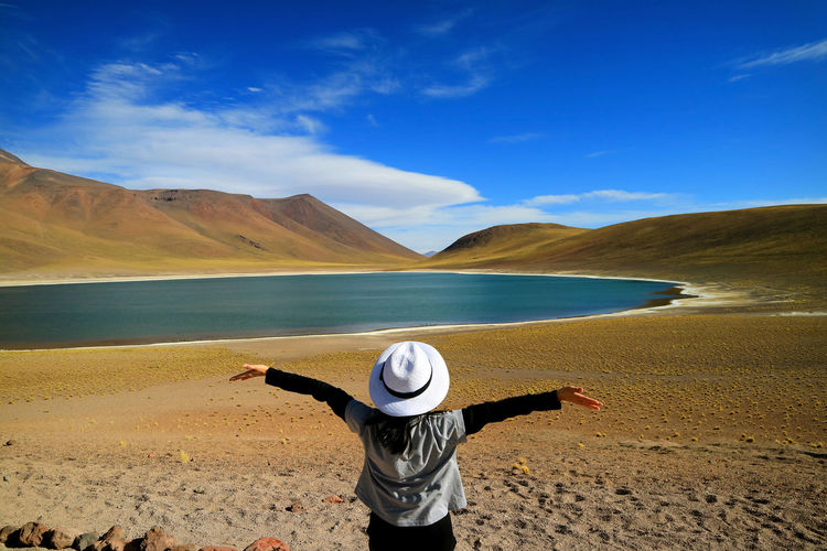 Rear view of mature woman with arms outstretched standing near lake against blue sky