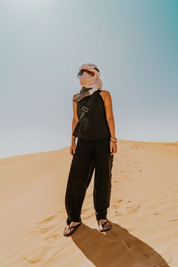 Full length of women wearing sunglasses with black dress and white turban standing on sand dune