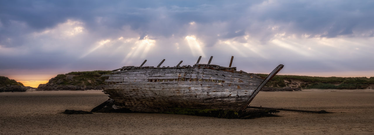 Panoramic shot of abandoned ship on beach against sky during sunset