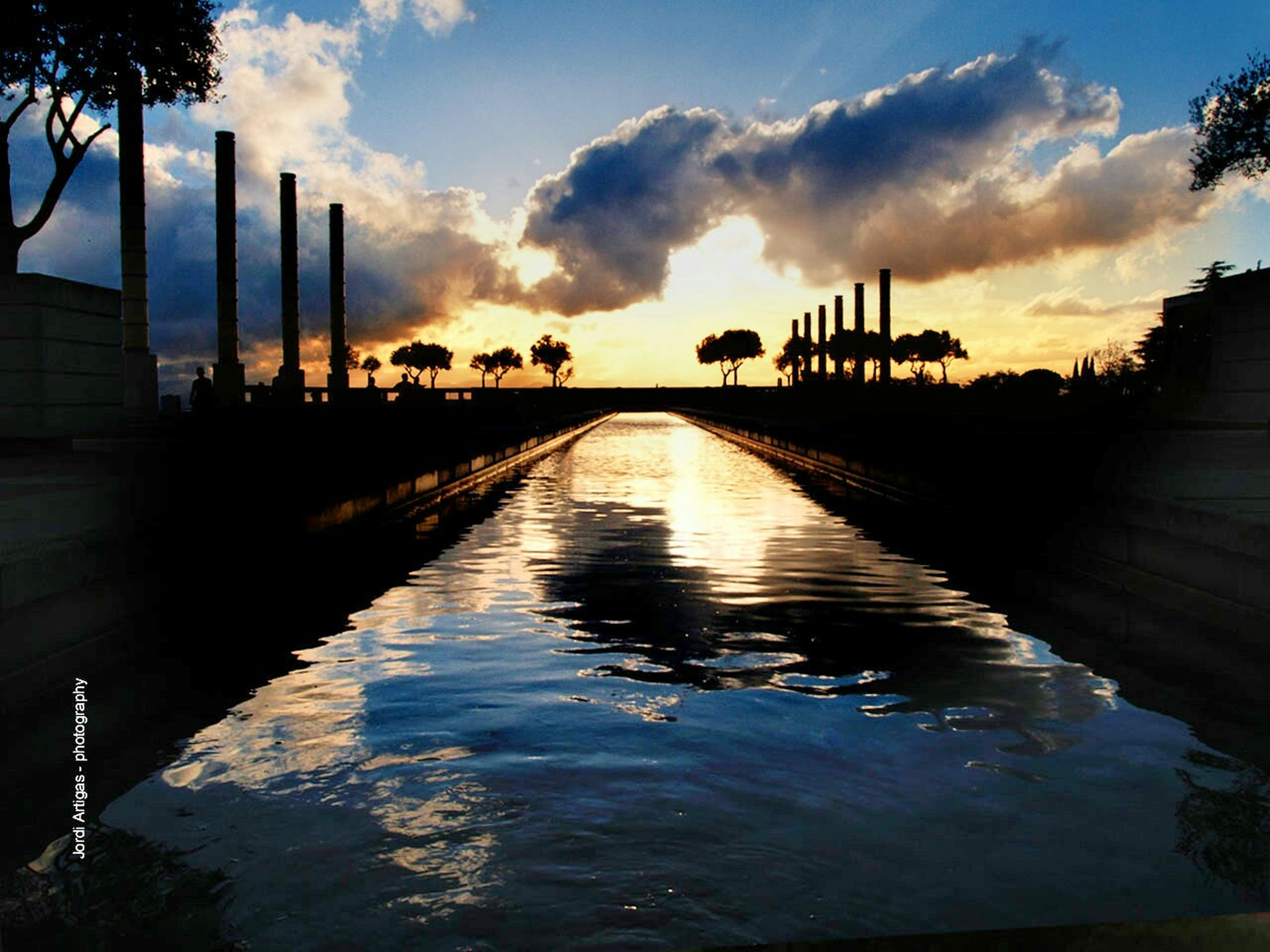 sunset, water, sky, built structure, architecture, cloud - sky, the way forward, diminishing perspective, connection, silhouette, reflection, river, waterfront, cloud, bridge - man made structure, building exterior, transportation, cloudy, vanishing point, nature
