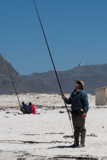 Men fishing on mountain against clear sky