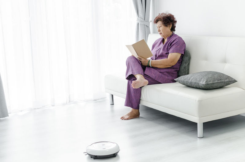 Woman reading book while lying on sofa at home