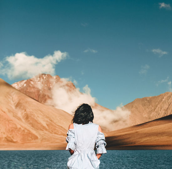 Rear view of woman standing by lake against mountain and sky