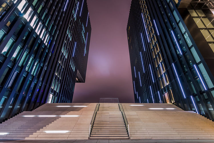 Low Angle View Of Steps Amidst Buildings Against Sky At Dusk
