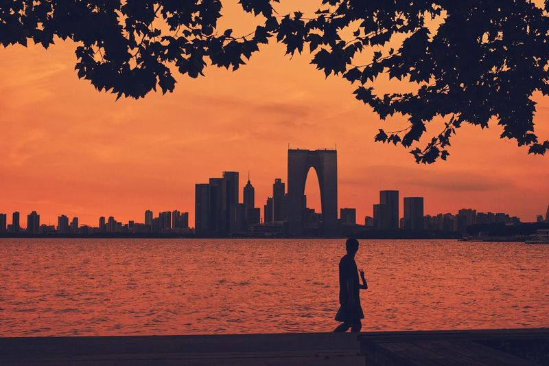 Silhouette of person standing by buildings against sky during sunset