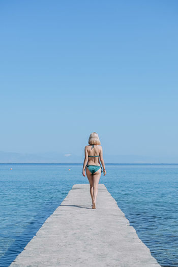 Full length of woman standing on sea against clear sky