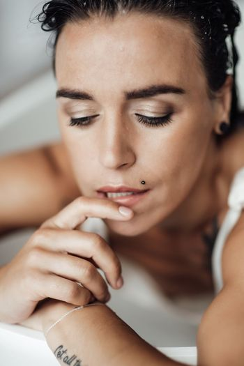 Close-up of woman face relaxing in bathtub