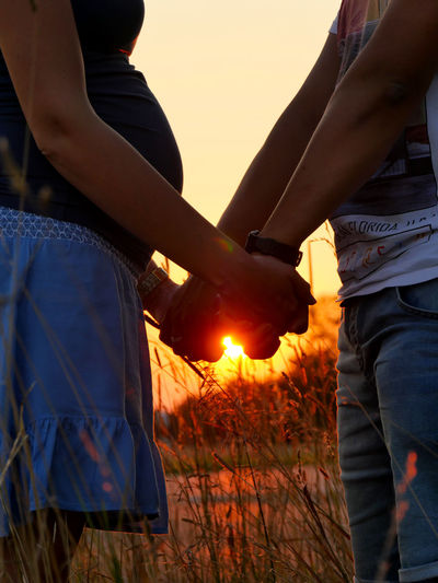 Midsection of couple holding hands against sky at sunset