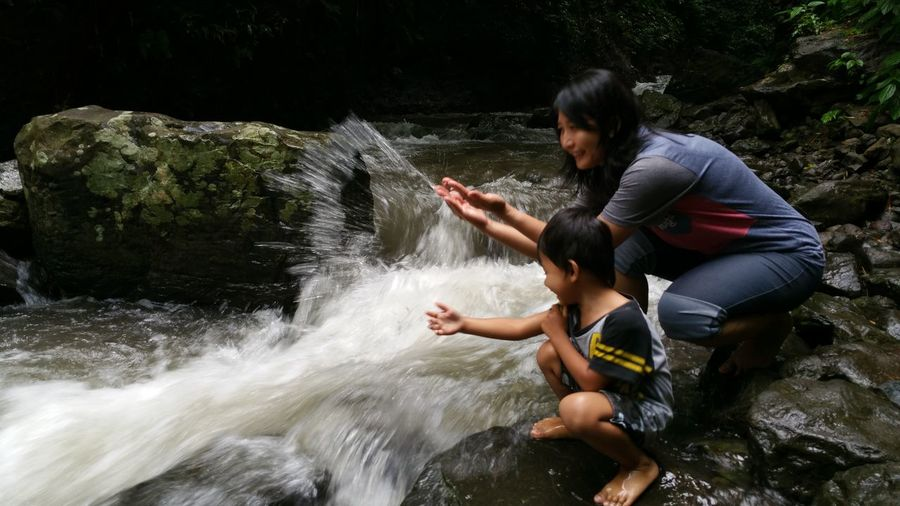 Mother And Son Splashing Water In Stream