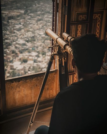 Rear View Of Man Looking Through Telescope