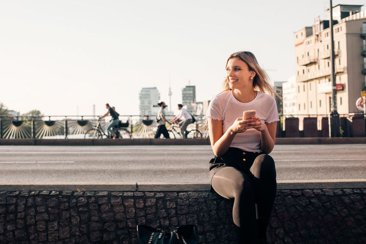 Young woman using phone while sitting on street in city
