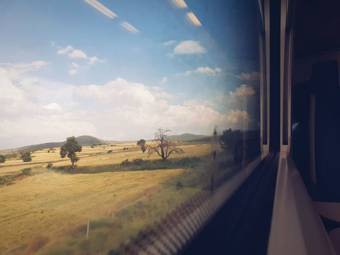 Panoramic view of landscape seen through train window