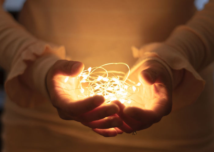 Close-up of hand holding illuminated lighting equipment