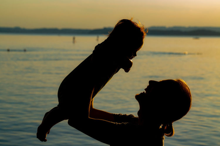 Silhouette Woman Holding Baby By Sea Against Sky During Sunset