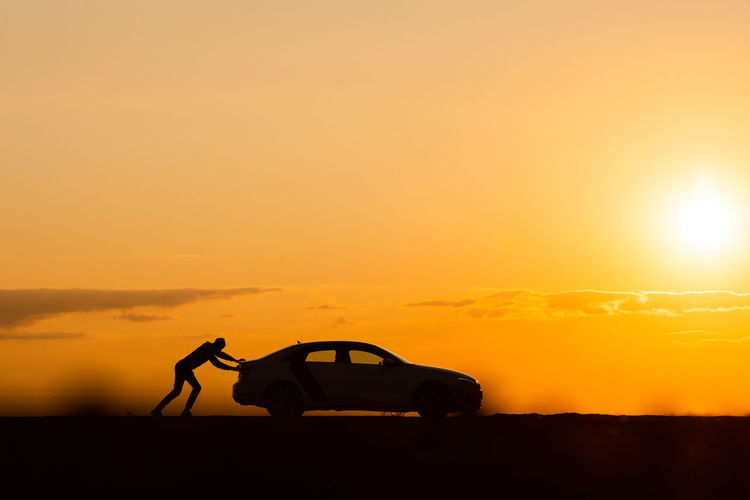 silhouette of man driver pushing his car along on an empty road after breakdown at sunset,