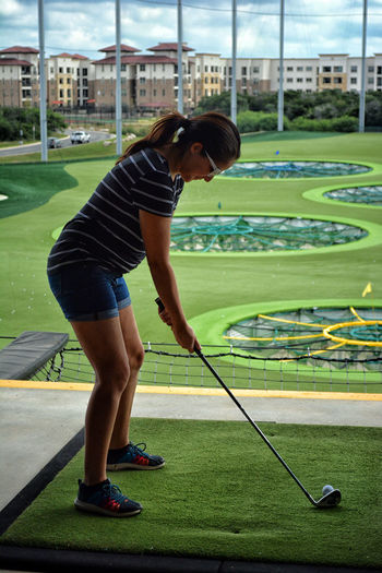 Full length side view of woman playing golf