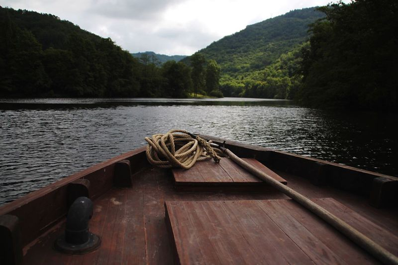 Rope on boat deck in river against mountains