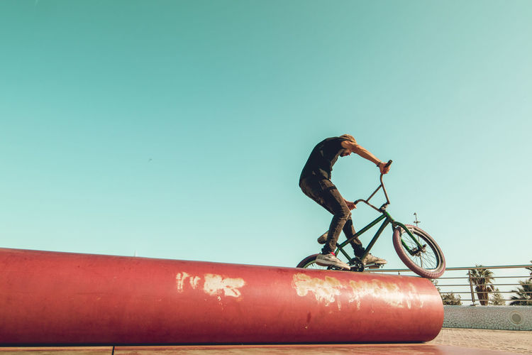 Man with bicycle against clear blue sky