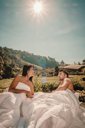 Shirtless Couple Lying On Bed With Landscape In Background Against Sky