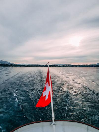 Swiss flag on a lake against sky