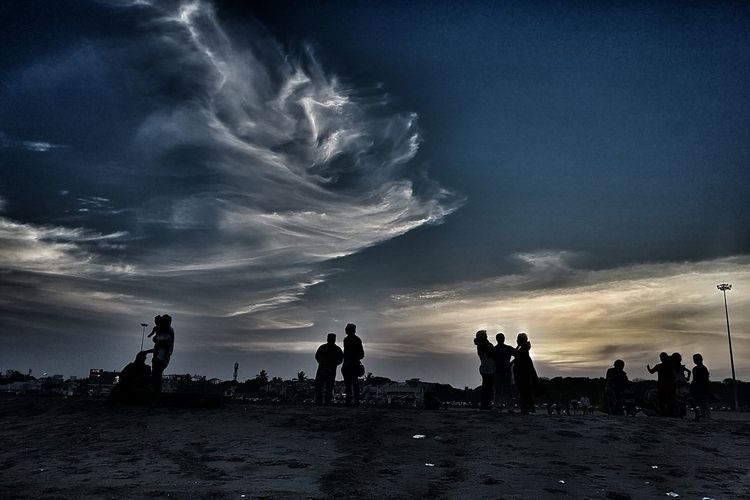 Silhouette people at beach against sky during sunset