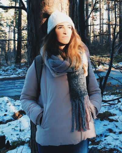 Portrait of woman standing by tree in forest during winter