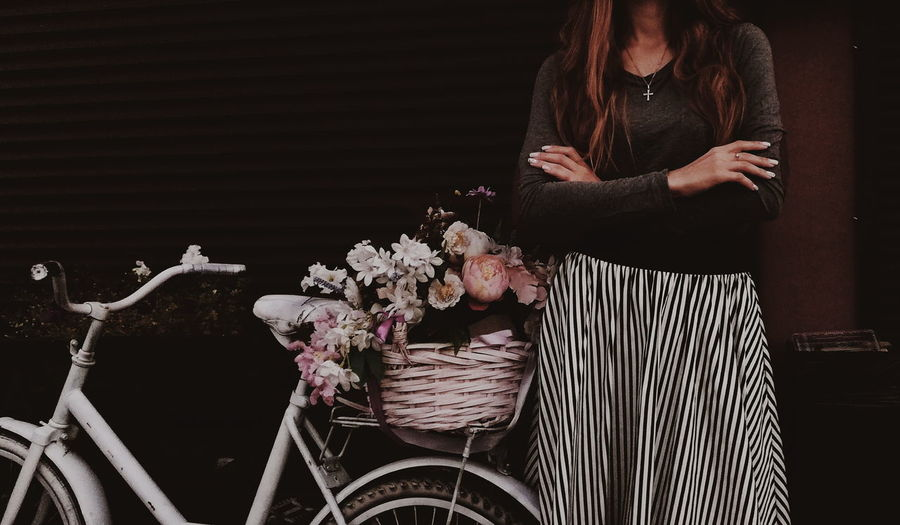 Midsection of woman standing by bicycle and flowers in city