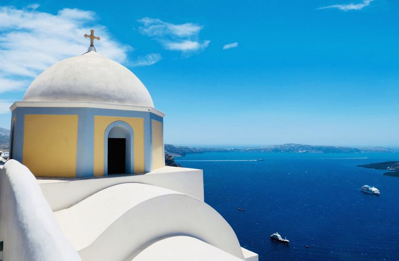Love Santorini ♥️ EyeEm Selects Water Dome Sea Religion Building Exterior Sky Architecture Belief Place Of Worship Built Structure Blue Nature Day White Color No People Spirituality Sunlight Horizon Over Water Outdoors EyeEmNewHere