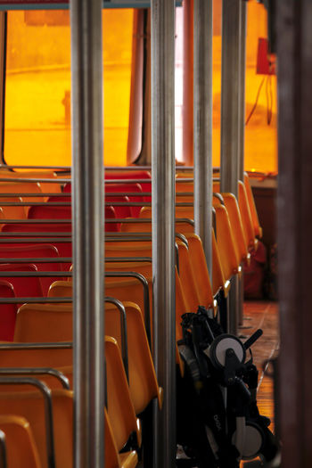 Orange chair on a passenger boat Absence Arrangement Chair Close-up Day Empty Full Frame In A Row Indoors  Large Group Of Objects Metal No People Orange Chair Series Orange Color Order Passenger Boat Repetition Seat Selective Focus Transparent Window