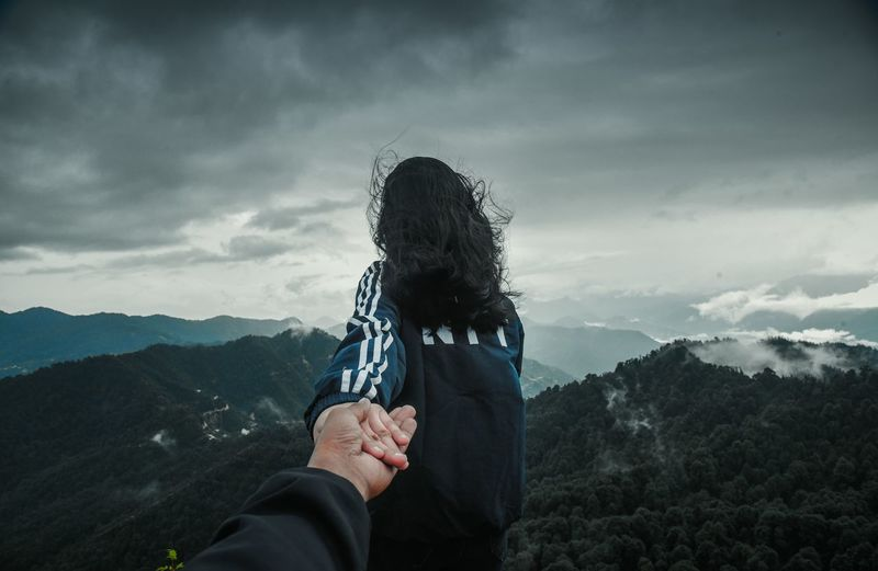 Cropped image of boyfriend holding girlfriend hand on mountain against sky