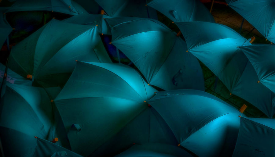 Full frame shot of turquoise umbrellas at night