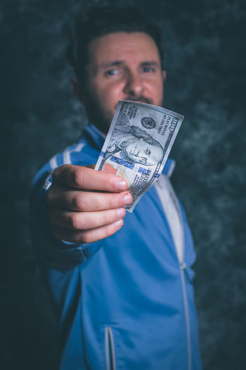 Portrait of man holding american one hundred dollar bill against wall