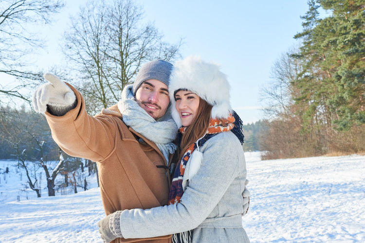 Couple standing on snow covered field