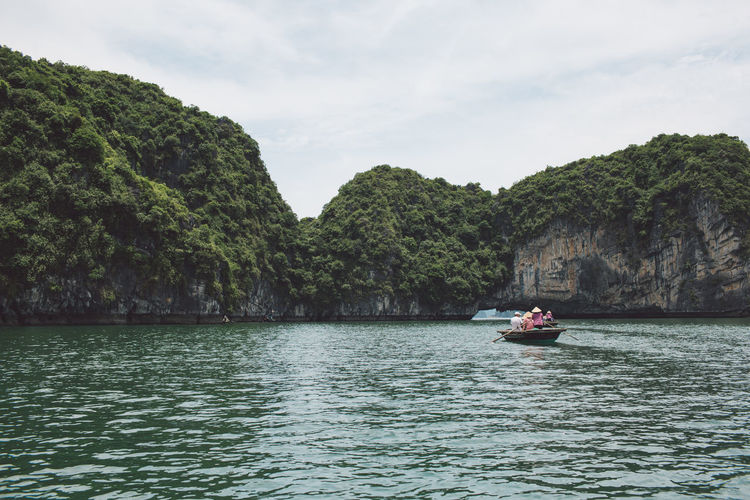People Rowing Boat On Halong Bay Against Rocky Mountains