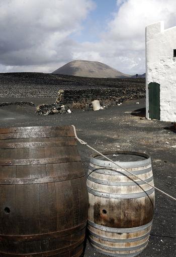 Wine casks on field against cloudy sky