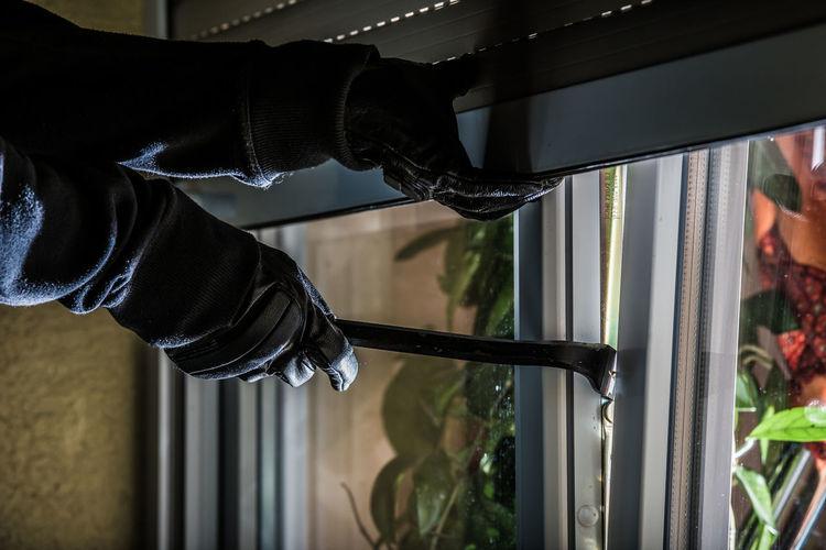 Cropped hands of burglar opening window
